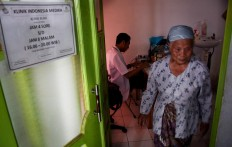 A resident walks out after getting treatment in the Indonesia Medika Clinic, Malang, East Java, on Tuesday (21/2). JP/ Aman Rochman