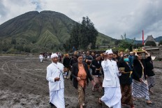 Two Hindu priests and people from the Hindu community walk around the Luhur Poten temple on Mount Bromo. JP/Tarko Sudiarno