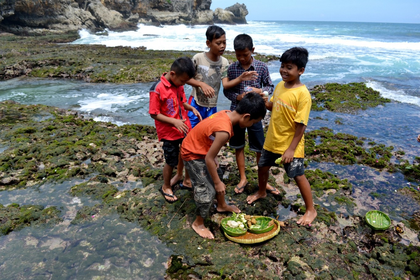 Children collect some of the offerings that were not washed away after the melasti ceremony finished.