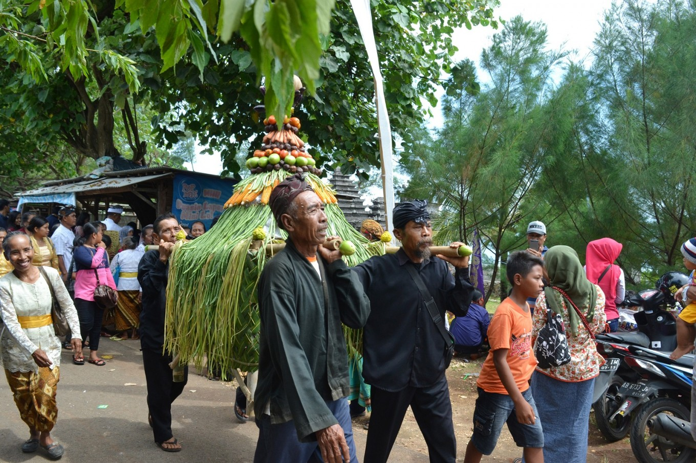 Gunungan (cone-shaped floats) are distributed to participants following the ceremony.