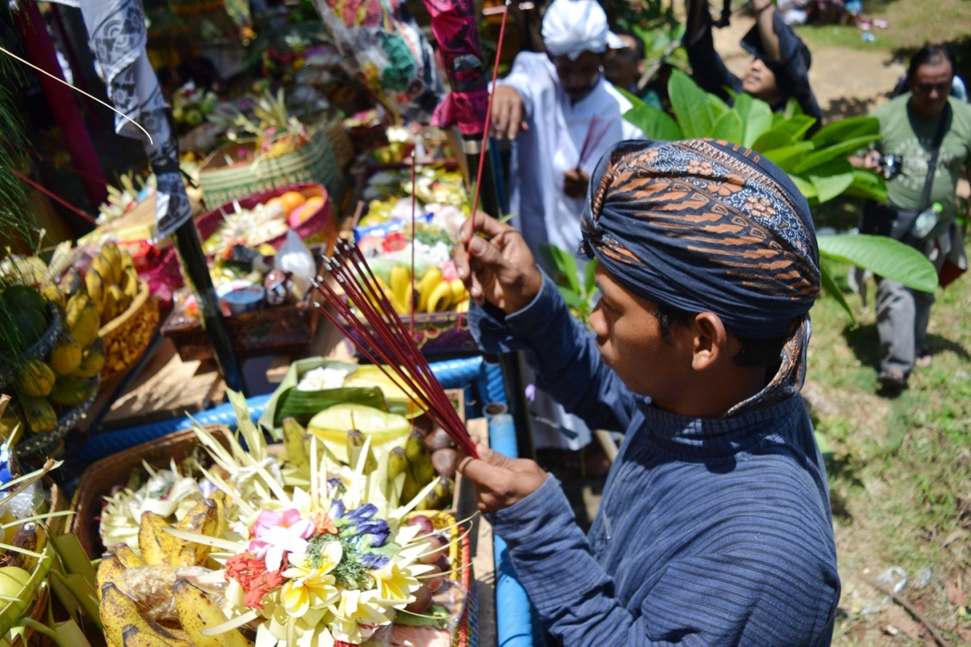 Incense sticks are added to offerings as part of the ritual.