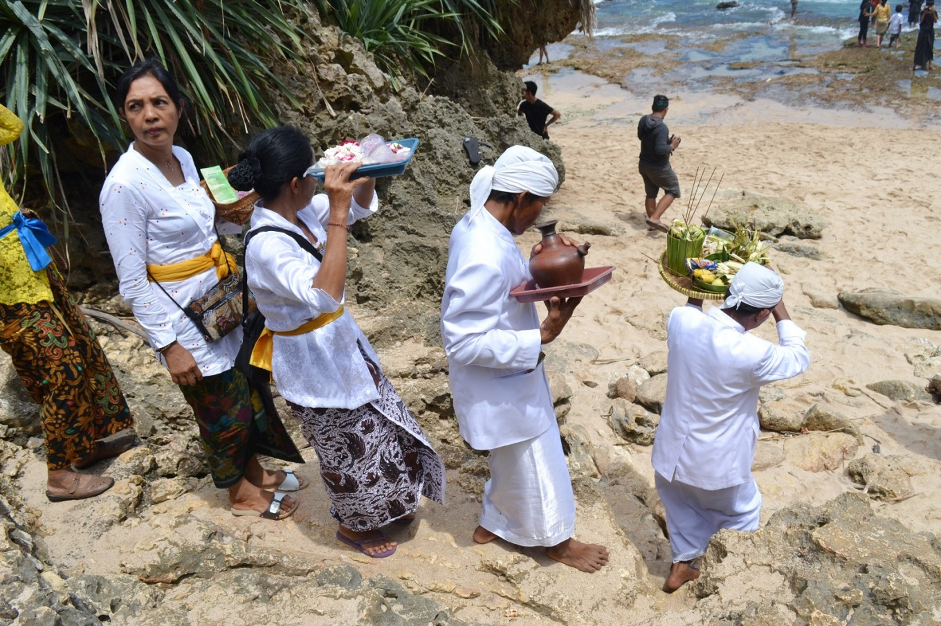 Melasti participants walk toward the shore for the larungan ritual.