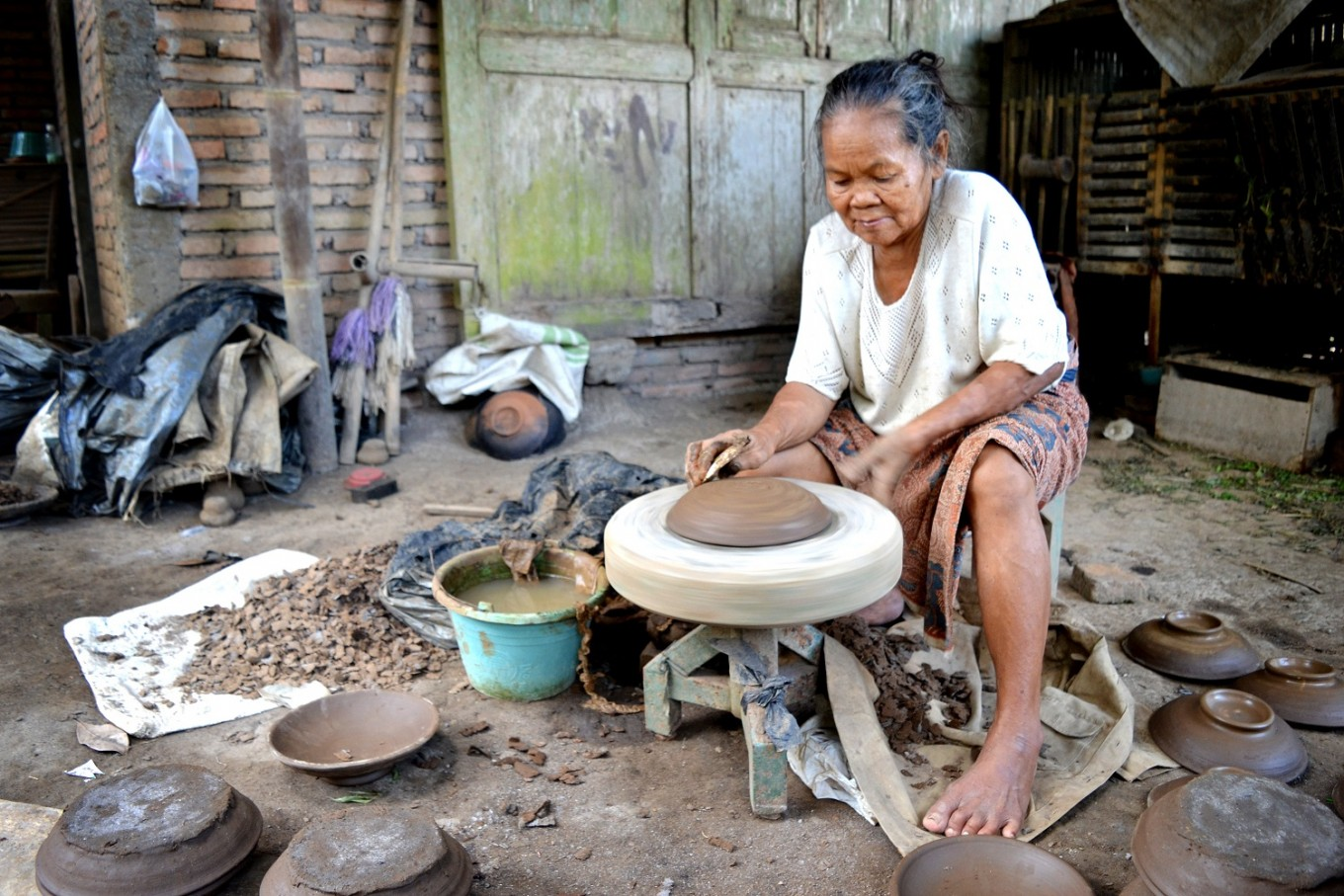 A woman is busy making a pottery in the house yard.