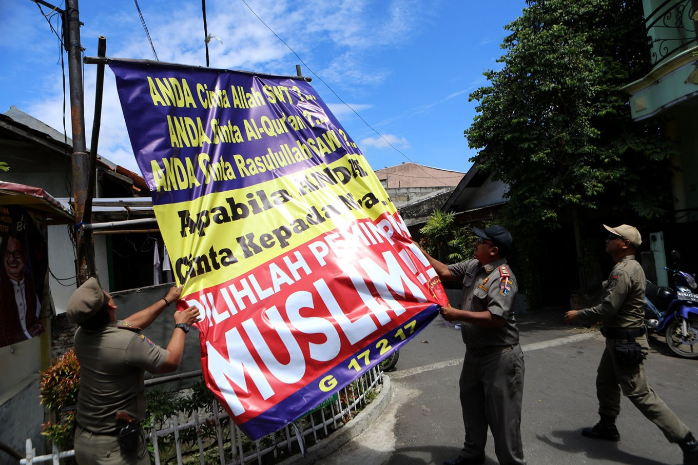 Jakarta officials remove provocative banners to reduce tension