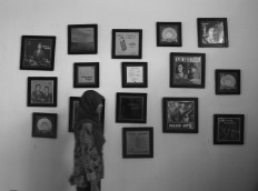 A visitor walks past pictures of musicians in one of Lokananta's rooms. JP/Ganug Nugroho Adi
