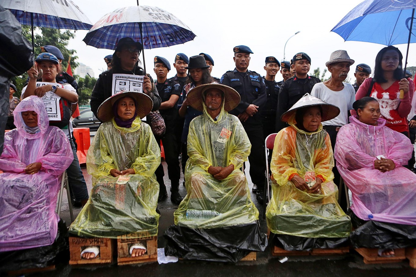 Activists with cemented feet greet First Lady in Pekanbaru