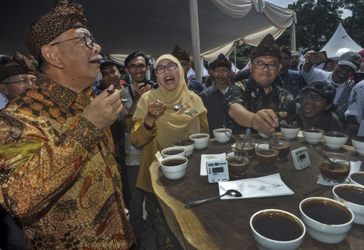 West Java Deputy Governor Deddy Mizwar (left) accompanies Governor Ahmad Heryawan (right) and his wife Netty Heryawan at a coffee event,