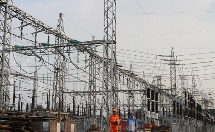 Two employees of state-owned electricity firm PLN walk at a power plant complex.