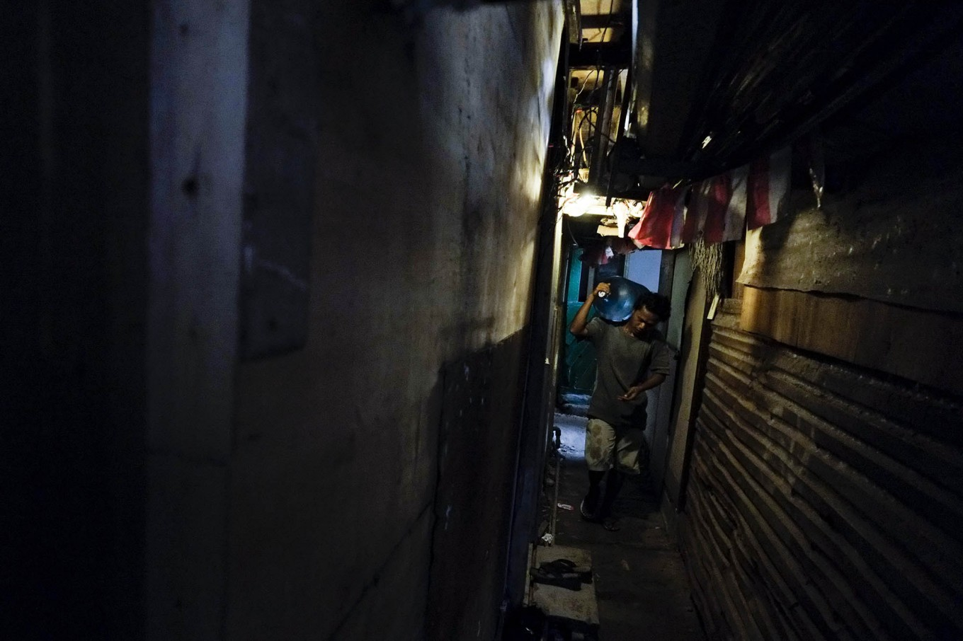 In dim light: Pio carries a water bottle to a customer's home through a narrow alley. JP/ Jerry Adiguna