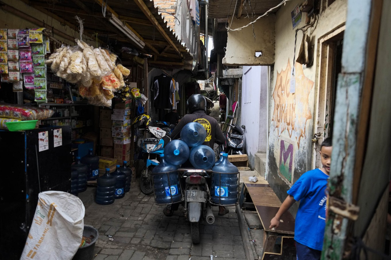 Getting through: Another water seller brings empty water bottles to a water agent for refilling in Ancol. Clean-water distribution has created a competitive small business in slum areas in North Jakarta. JP/ Jerry Adiguna