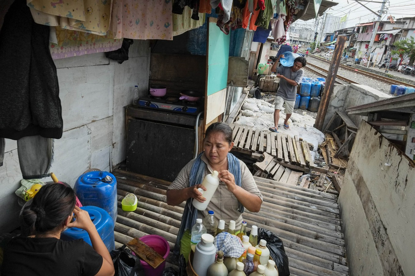 Manual work: Pio (back) carries a full water bottle while a jamu (traditional herbal drinks) seller serves her customer in a densely populated area of Kampung Muka. JP/ Jerry Adiguna