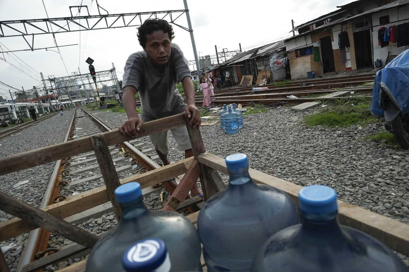 Heavy load: Pio pushes his cart of water bottles on a railway line in Kampung Muka, Ancol, North Jakarta. He has to memorize the train schedules to allow him to use his cart on the track safely. JP/ Jerry Adiguna