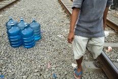 Pilling up: Pio stocks his bottles in the space between two railway tracks while waiting for a train to pass. JP/ Jerry Adiguna