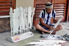 Khotib uses sandpaper to smoothen the wood of wayang klitik. JP/ Magnus Hendratmo