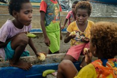 Kamoro children eat fruit from the offerings. JP/Vembri Waluyas