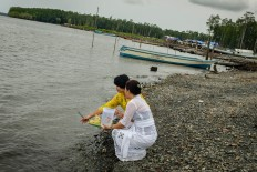 Two women float the offerings out to sea. JP/Vembri Waluyas