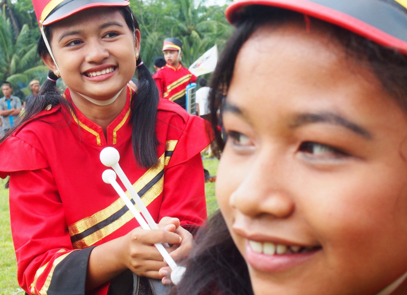 Two female marching band members smile before getting ready for the celebration. JP/Ganug Nugroho Adi