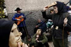 In this April 1, 2017 picture revelers from San Pedro Bernardo village wearing the traditional 'Machurrero' mask and outfit rest after a parade during a gathering of different villages' carnival masks and characters in the small village of Casavieja, Spain, Monday, April 3, 2017. AP /Daniel Ochoa de Olza