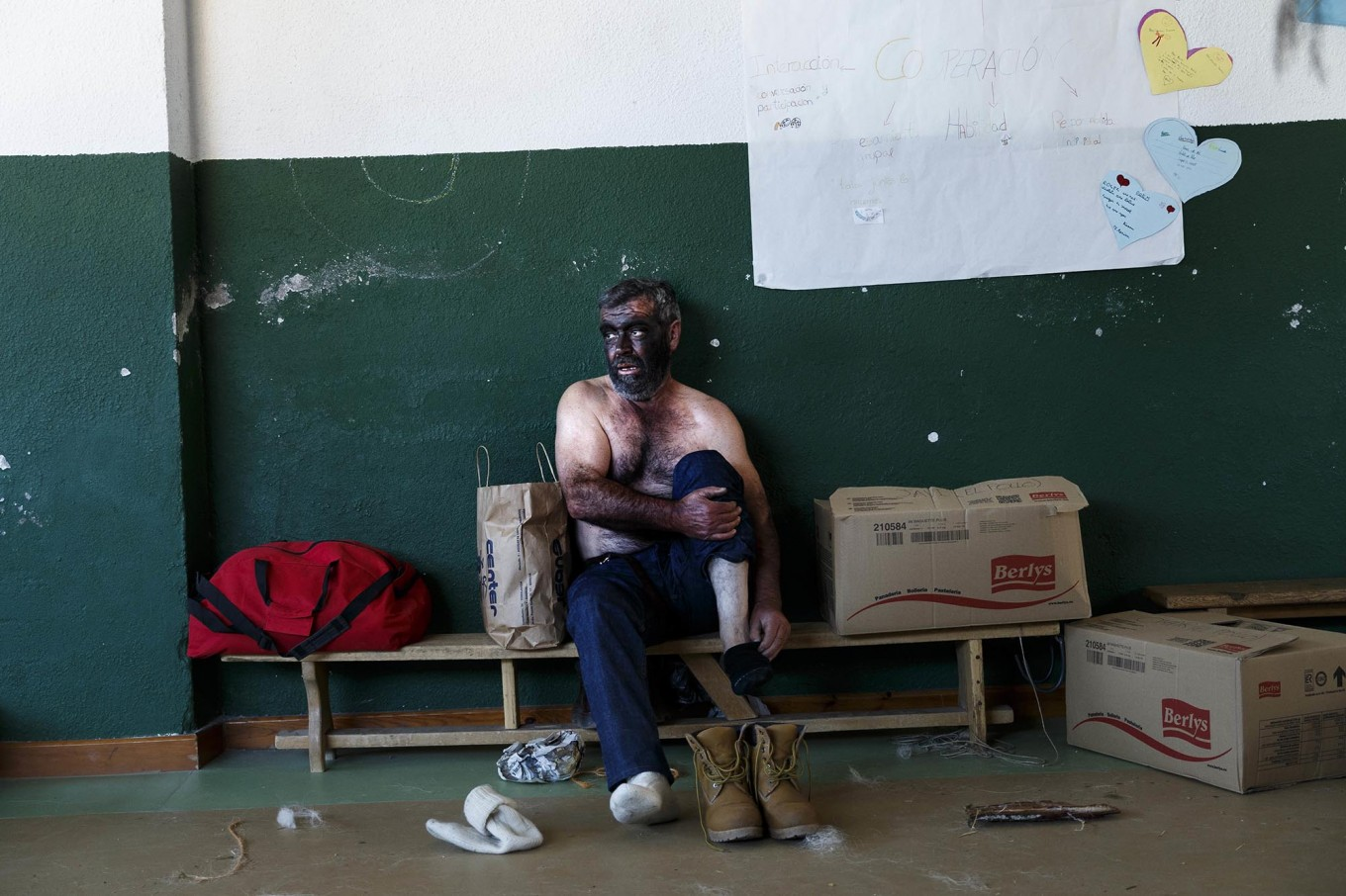In this April 1, 2017 picture a man takes off his sock after performing as a 'Zarramaco' a character that stains his face in black and rings cowbells in representation of the traditional carnival of La Vijanera de Silio during a gathering of different villages' carnival masks and characters, in Casavieja, Spain, Monday, April 3, 2017. These festivals, held across central and northwestern Spain, most often coincide with festivities celebrating the advent of spring, mixing Carnival and bizarre pagan-like rituals with mock battles between good and evil. AP/Daniel Ochoa de Olza