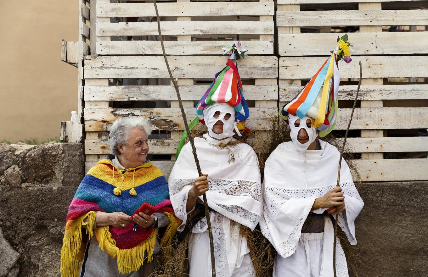 In this April 1, 2017 picture a woman speaks with a couple of youngsters dressed as 'Zarramaches' a character from the traditional carnival of Casavieja, during a gathering of different villages' carnival masks and characters, in Casavieja, Spain, Monday, April 3, 2017. These festivals, held across central and northwestern Spain, most often coincide with festivities celebrating the advent of spring, mixing Carnival and bizarre pagan-like rituals with mock battles between good and evil. AP /Daniel Ochoa de Olza
