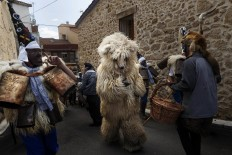 In this April 1, 2017 picture a man looks as 'Zarramacos' dong their cowbells in a representation of the traditional carnival of La Vijanera de Silio during a gathering of different villages' carnival masks and characters, in Casavieja, Spain, Monday, April 3, 2017. AP /Daniel Ochoa de Olza