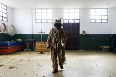 In this April 1, 2017 picture a man dressed as a 'Trapajon' and representing a natural entity walks in the village's gym used as a changing room after a traditional Spanish mask gathering in the small village of Casavieja, Spain, Monday, April 3, 2017. These festivals, held across central and northwestern Spain, most often coincide with festivities celebrating the advent of spring, mixing Carnival and bizarre pagan-like rituals with mock battles between good and evil. AP /Daniel Ochoa de Olza