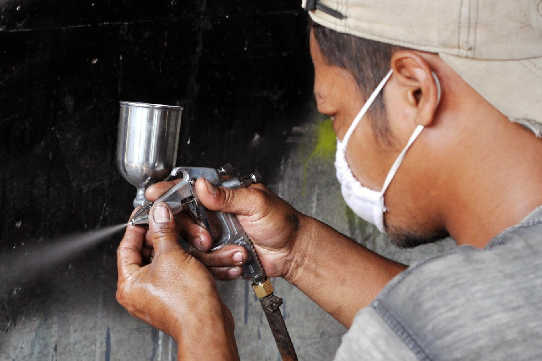 A worker sets the air pressure of a paint sprayer. JP/Magnus Koeshendratmo