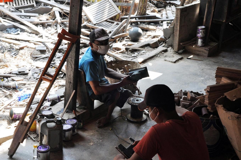 Two men work on making crosses at Widodo's workshop. JP/Magnus Koeshendratmo