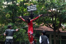 Congregants of Santa Theresa Church in Bojongsari, Semarang, Central Java, watch a performance depicting the crucifixion of Jesus Christ [portrayed by Yohannes Dendi] on Good Friday. JP/Suherdjoko