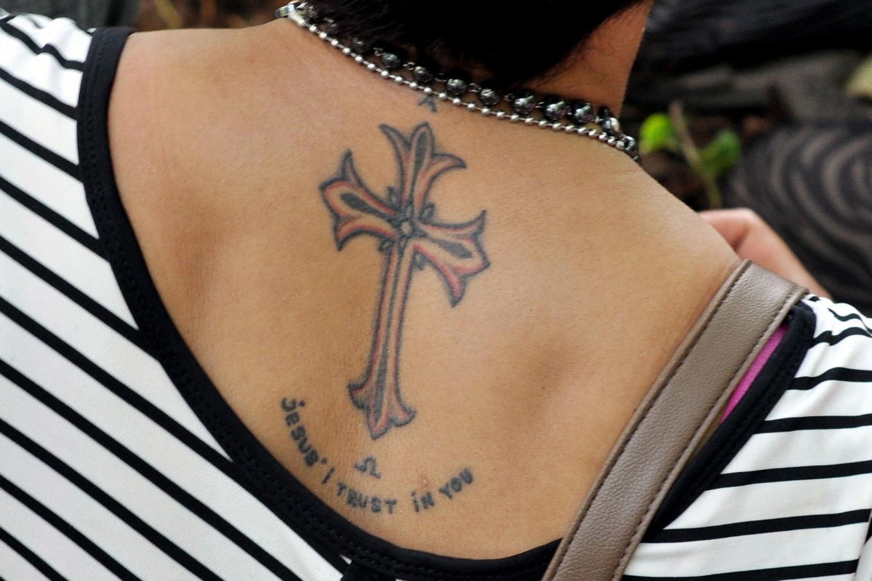 A congregant displays a tattoo of a cross on her back at Yohanes Rasul church, Wonogiri, Central Java on Friday April 14.  JP/Magnus Hendratmo