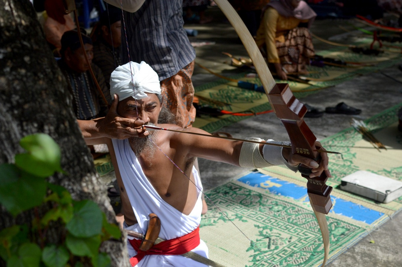 The archers take aim from a sitting position and wear traditional Javanese attire during competitions.