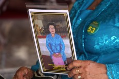 A participant holds a picture of herself that she bought from a photographer after her performance.  JP/Aditya Sagita