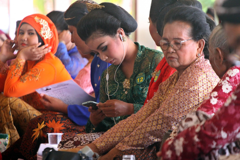 A contestant listens to macapat using earphones while waiting for her turn. JP/Aditya Sagita