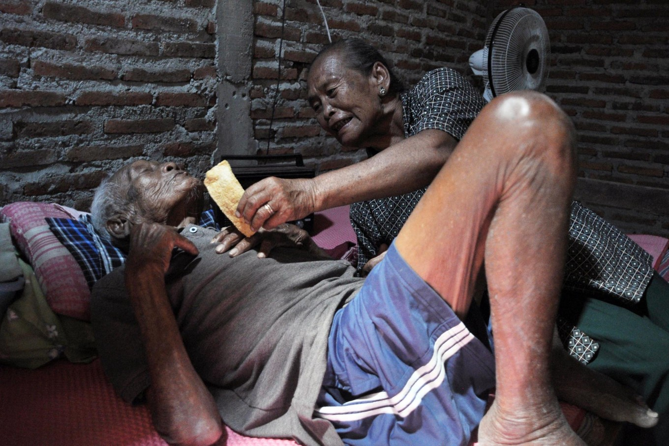 Sugiyem gives a rice cracker to his father. Rice crackers were Mbah Jo Gotho's favorite snack. JP/Magnus Hendratmo