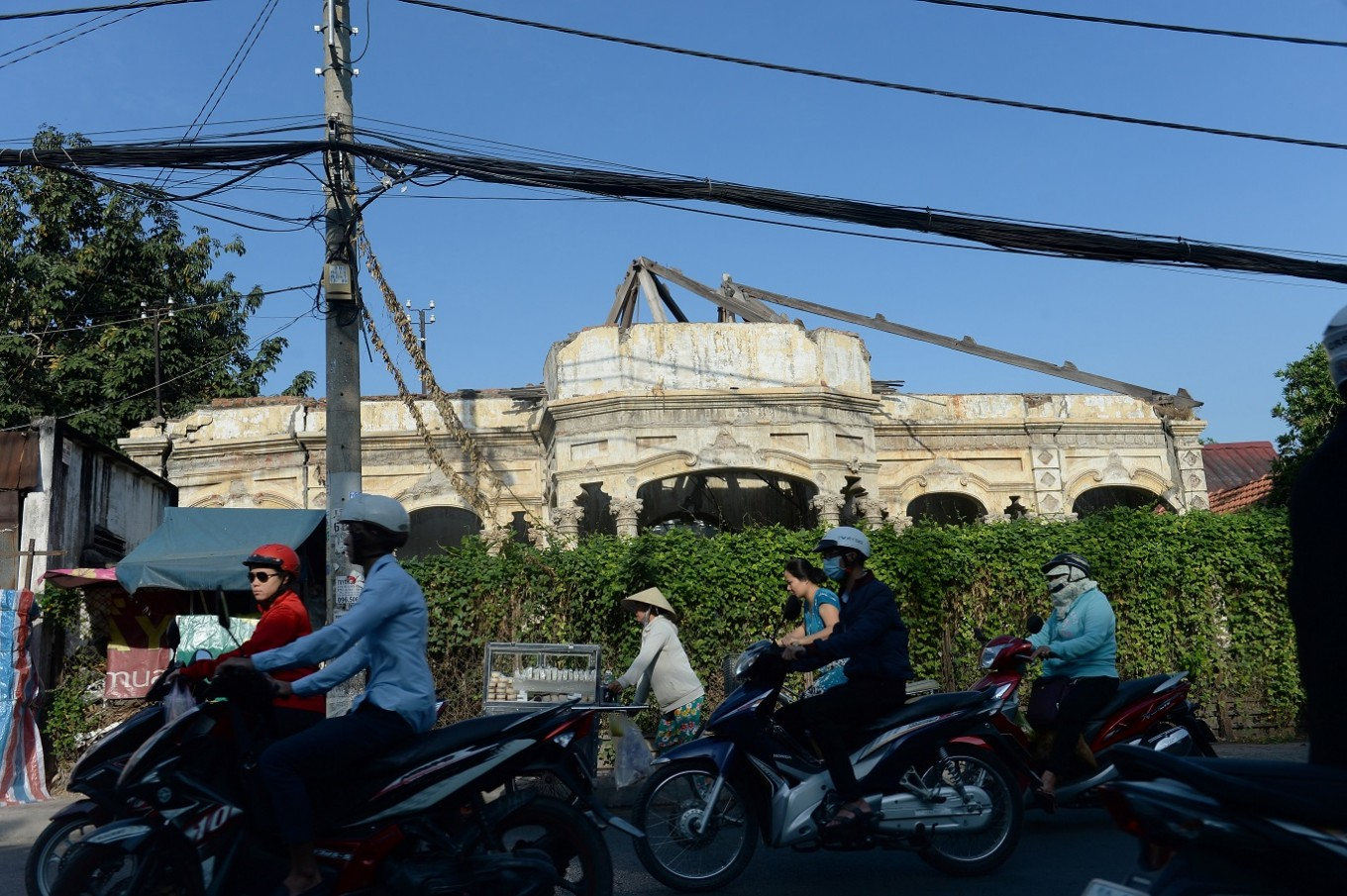 "This picture taken on February 21, 2017 shows motorcyclists riding past a French colonial-era ruined house in Ho Chi Minh City (former Saigon). They formed the charming backdrop to Graham Greene's sin-filled city in ""The Quiet American"" but Saigon's colonial buildings are fast disappearing, sparking fears Vietnam's biggest city is becoming another generic Asian megalopolis."