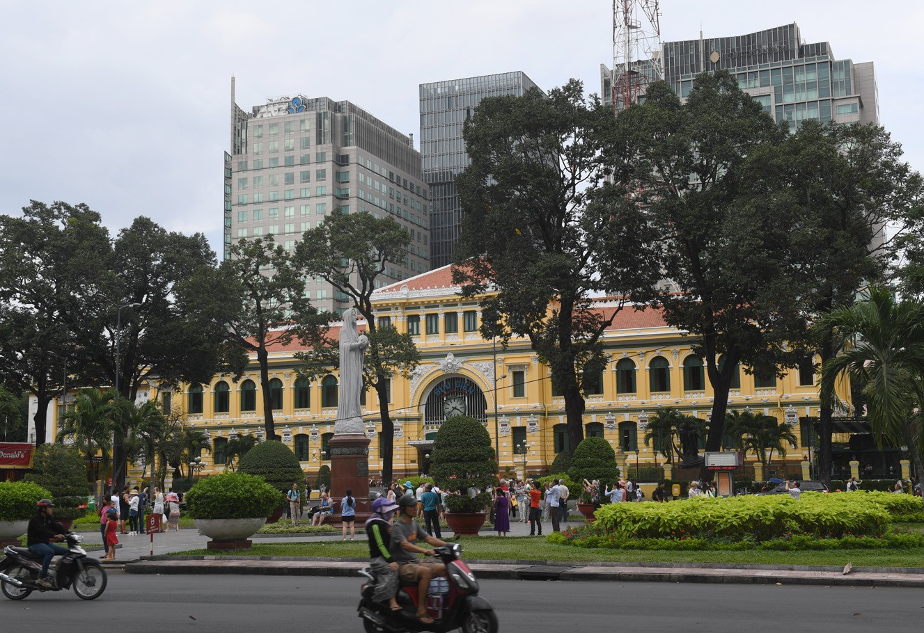 "This picture taken on February 21, 2017 shows new high buildings (background) looming over the French-colonial era Post Office in downtown Ho Chi Minh City (former Saigon). They formed the charming backdrop to Graham Greene's sin-filled city in ""The Quiet American"" but Saigon's colonial buildings are fast disappearing, sparking fears Vietnam's biggest city is becoming another generic Asian megalopolis."