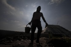 A woman carries a bucket of clay to be molded. She can mold up to 1,500 bricks per day.  JP/Sigit Pamungkas