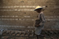 A craftsman moves some dried bricks to be fired after they have been drying under the sun. JP/Sigit Pamungkas
