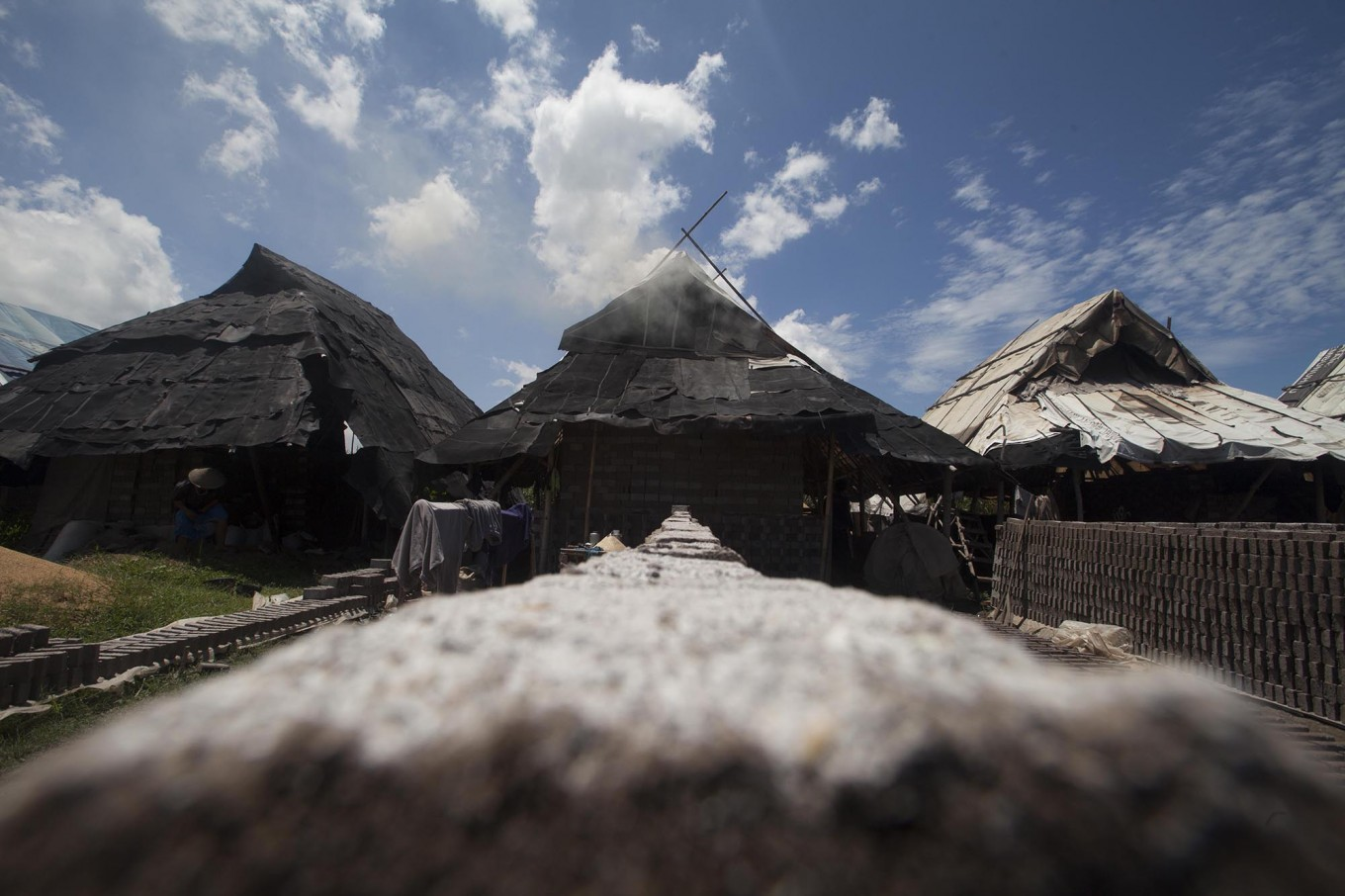 Three huts are used by brick makers to protect the bricks from rain during the firing process.  JP/Sigit Pamungkas