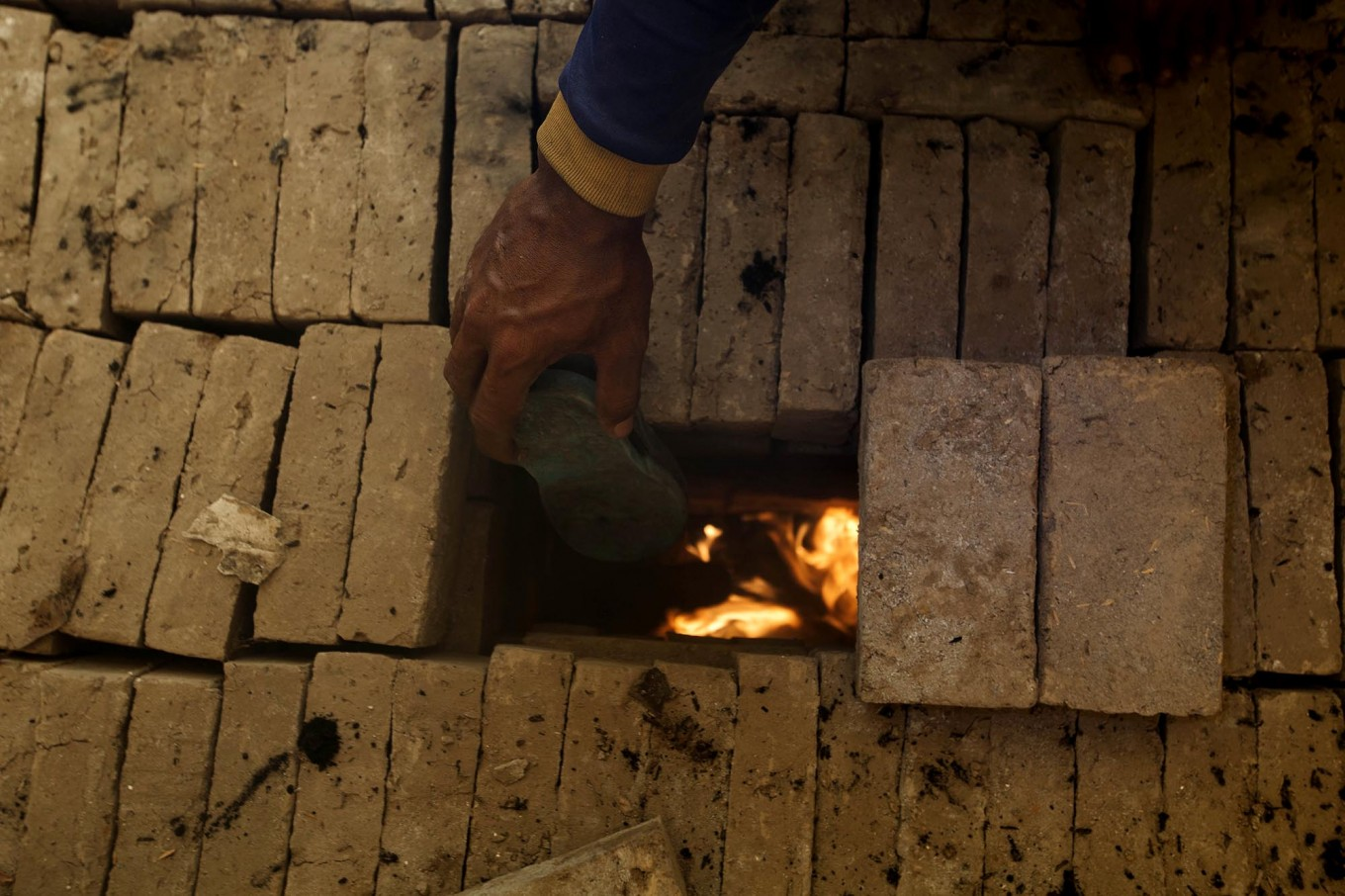 A craftsman puts an old rubber sandal and husk into a traditional stove to stoke a good fire with a high temperature for firing the bricks. JP/Sigit Pamungkas