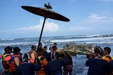 Dozens of Yogyakarta Palace royal servants and the search and rescue staff carry offerings to be thrown into the sea on April 27, 2017. The offerings include batik, which signifies the coronation anniversary of Hamengkubuwono X. JP/Tarko Sudiarno