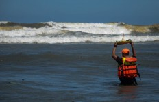 A search and rescue staff member throws an offering into the ocean during the Labuhan ceremony at Parang Kusumo Beach, Yogyakarta, on May 19, 2015. JP/Tarko Sudiarno