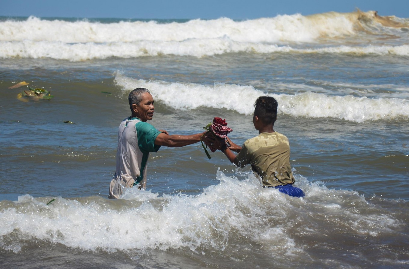 Men collect some of the offerings at Parang Kusumo Beach, Yogyakarta, on May 19, 2015.  JP/Tarko Sudiarno