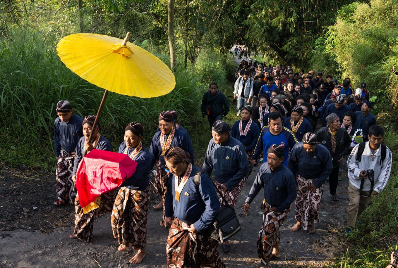 Dozens of Yogyakarta Palace royal servants carry offerings along a trail to Mount Merapi during the Labuhan ceremony on April 28, 2017. JP/Tarko Sudiarno