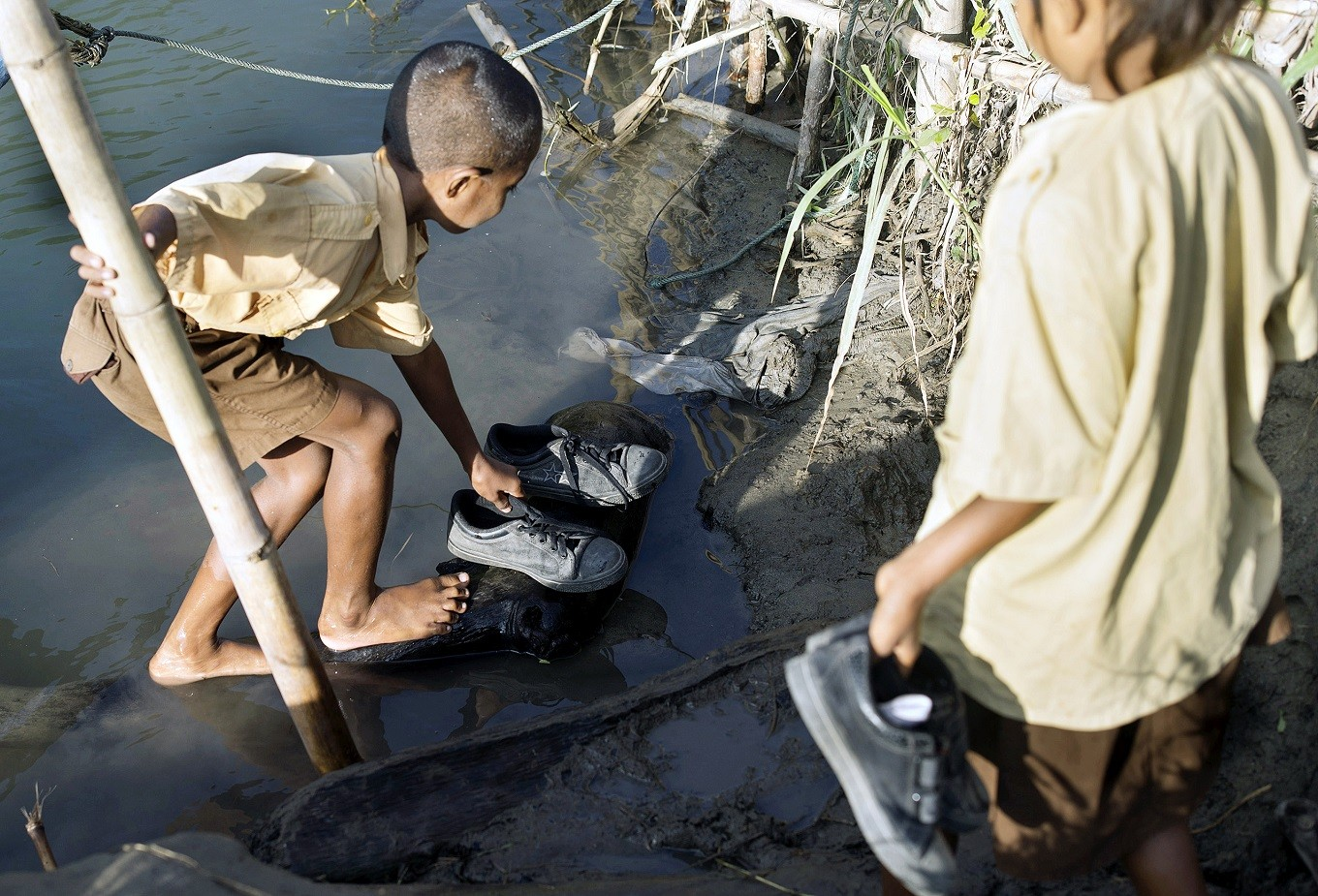 Tidy up: A child laces his shoes after crossing a 65-meter-wide river.