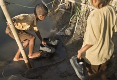 Tidy up: A child laces his shoes after crossing a 65-meter-wide river. JP/ Tarko Sudiarno