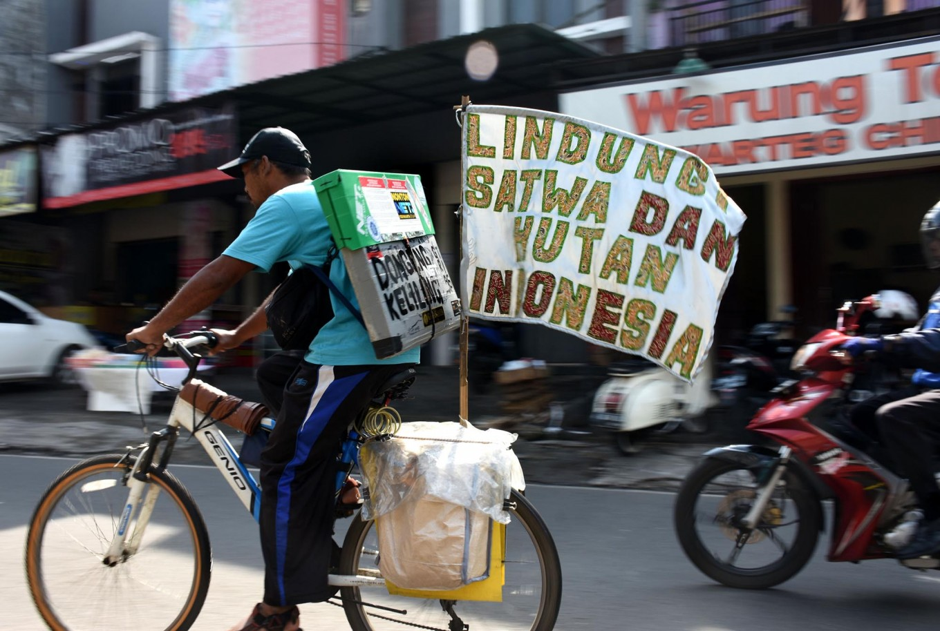 Samsudin rides a bicycle on his journey to tell stories about forests and animals to children in cities across Indonesia. JP/Aman Rochman