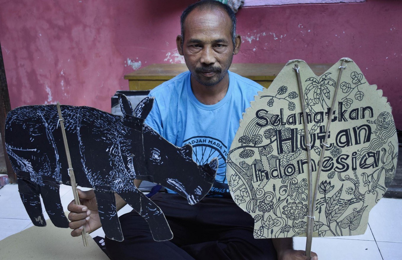 Samsudin poses with cardboard cutouts after storytelling at the kindergarten on April 4. JP/Aman Rochman