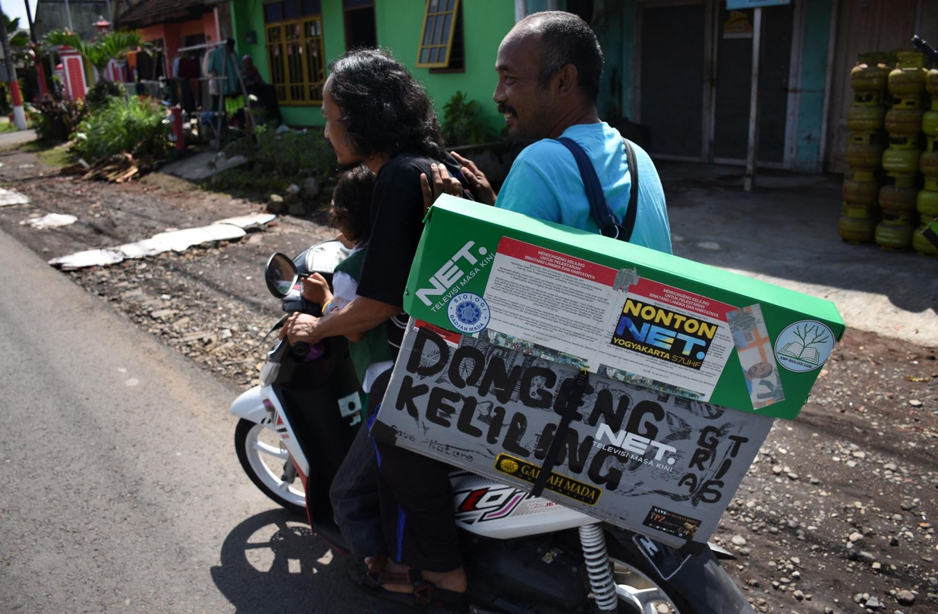 A volunteer rides a motorcycle to help Samsudin on his storytelling tour in Malang, East Java, on April 4. JP/Aman Rochman