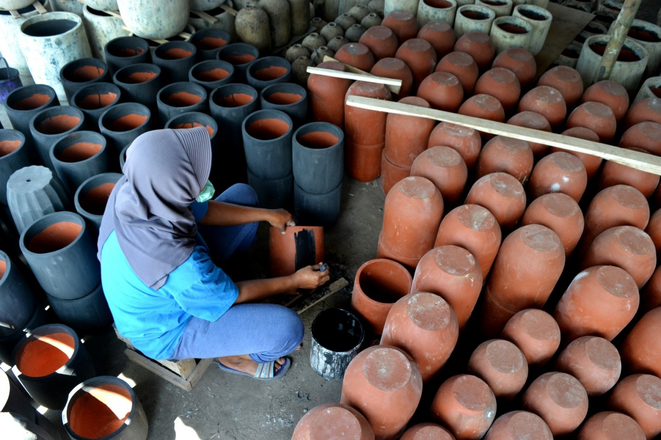 A worker adds color to rustic-style pottery.